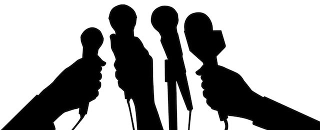 Silhouette of journalists' hands with microphones